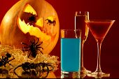 foto of antichrist  - Image of glasses with colorful drinks on background of Halloween pumpkin with spiders on it - JPG