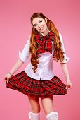 picture of up-skirt  - Cute smiling teen girl in school plaid skirt and white blouse posing over pink background - JPG
