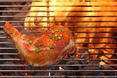 picture of flame-grilled  - Grilled Glazed Chicken Quarter On The Hot BBQ Charcoal Flaming Grill Close - JPG