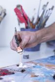 picture of paint palette  - closeup of the hand of a male painter adding paint to the palette at his painting studio  - JPG