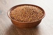 picture of ceramic bowl  - Full ceramic bowl with buckwheat on wooden background - JPG