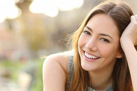 image of emotion  - Woman smiling with perfect smile and white teeth in a park and looking at camera - JPG