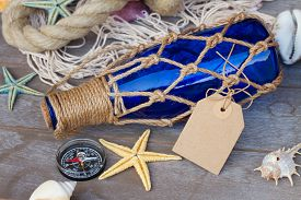foto of marines  - marine bottle with with  fishing net  and marine rope on wood - JPG