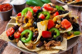 picture of jalapeno  - Plate of Mexican nachos loaded with ground meat jalapenos tomatoes beans and melted cheese - JPG