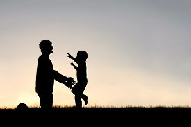 picture of hug  - Silhouette of a happy young child smiling as he runs to greet his father with a hug at sunset on a summer day - JPG