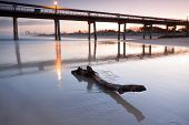 Log On Beach At Twilight With Pier And The City