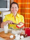 foto of margarine  - Smiling woman adds margarine into dough in kitchen - JPG