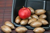 stock photo of pecan tree  - pecans and apples in a bowl on a bamboo mat - JPG