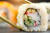 Eating Sushi with chopsticks. Sushi roll japanese food in restaurant. California Sushi roll set with poster