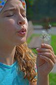 Girl and dandelion wish