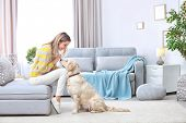 Portrait of happy woman with her dog at home poster