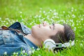 Young Man Relaxing Smiling While Lying On Grass And Listening To Music With Headphones .player,relax poster