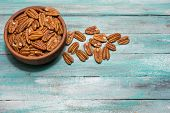 Tasty Pecan  In Wooden Bowl On The Old Background. poster