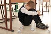 Upset little boy sitting on floor indoors. Bullying in school poster