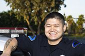 stock photo of lightbar  - an Asian police officer standing next to his patrol car as he smiles - JPG