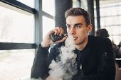 Young Man Vaping In Closed Public Space.smoking Electronic Cigarette In Cafe.nicotine Addiction.way  poster