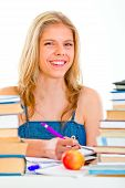 Cheerful Teen Girl Sitting At Table With Lots Of Books