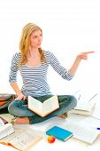 Cheerful Teen Girl Sitting On Floor Among Schoolbooks And Pointing In Corner poster