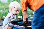 Child With Blue Eyes Playing In The Mud In The Summer On The Street poster
