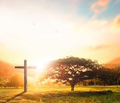 Concept Conceptual Black Cross Religion Symbol Silhouette In Grass Over Sunset Or Sunrise Sky poster