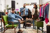 sale, shopping, fashion and people concept - friends choosing clothes and footwear at vintage clothi poster