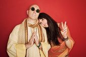 stock photo of swami  - Pious guru prays with woman makes peace symbol - JPG