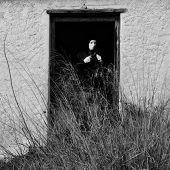 stock photo of pervert  - Masked figure by broken door of abandoned house obscured by overgrown plants - JPG