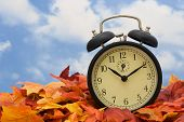 stock photo of tick tock  - Retro clock on fall leaves sky background - JPG