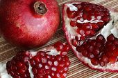 Pomegranate Fruit Cut In Half. Bright Juicy Ripe Pomegranate Seeds. poster