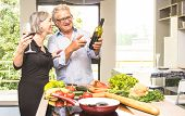 Senior Couple Cooking Healthy Food And Drinking Red Wine At House Kitchen - Retired People At Home P poster