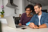 Smiling young couple making shopping online with credit card and laptop at home. Happy multiethnic c poster