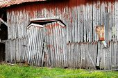 stock photo of sag  - Sagging double doors barely hang on their hinges on this rustic barn - JPG