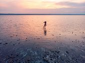 Silhouette Of A Girl In The Middle Of Lake At Sunset. Beautiful Girl Posing Alone In Shallow Water W poster