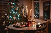 New Year Night Table Decoration With Candles And Antique Decorations On The Background Of Lights And poster