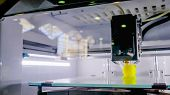 Three Dimensional Printing Machine Printing Yellow 3d Plastic Model At Modern Technology Exhibition. poster