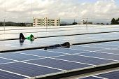 Technicians Arranging Cable Under Pv Modules Of A Solar Rooftop System poster