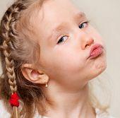 Grimacing child. Capricious little girl.