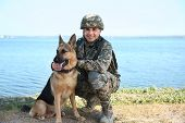 Man In Military Uniform With German Shepherd Dog Near River poster