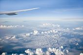 Wing Of The Plane On Blue Sky Background. View Of The Clouds From An Airplane. Aerial View Of Blue S poster