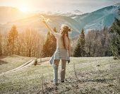 Young aviator girl with her airplane toy starting fly. Beautiful spreeng mountains view at sunny day poster