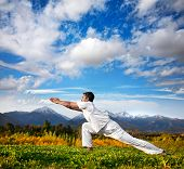 foto of virabhadrasana  - Yoga virabhadrasana warrior pose by Indian Man in white cloth in the morning at mountain background - JPG