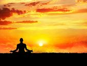 pic of samadhi  - Yoga meditation in lotus pose by man silhouette at sunset sky background - JPG