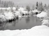 Snow Falling On A River With Snowy Banks In Whistler British Columbia