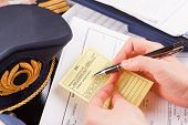 Close up of an airplane pilot hand holding medical certificate with equipment including hat, epaulet