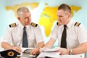 Two airline pilots preparing to flight, checking papers flight plan, log book. Pilots are sitting in