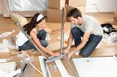 Couple moving in together assembling furniture table. Young interracial couple in new house or apart