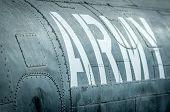 Vista lateral de un avión militar con inscripción.