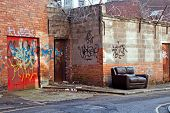 stock photo of settee  - Abandoned couch in inner city graffiti covered alleyway - JPG