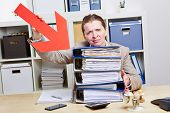 Business woman with burnout pointing arrow to files in her office