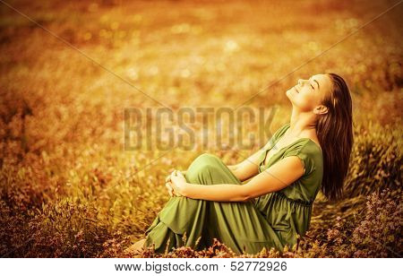 Romantic woman wearing long elegant dress sitting on golden dry field, autumn season, relaxation in  poster
